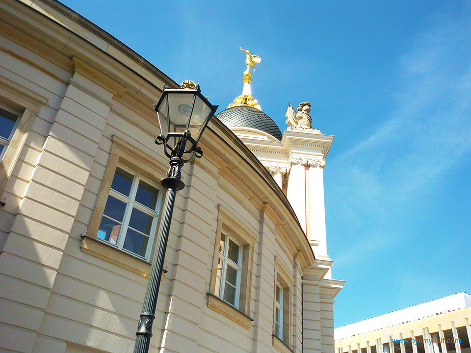 A gilded statue of Fortuna on top of the entrance gate to the Stadtschloss in Potsdam, the great small town, introduced in this guide