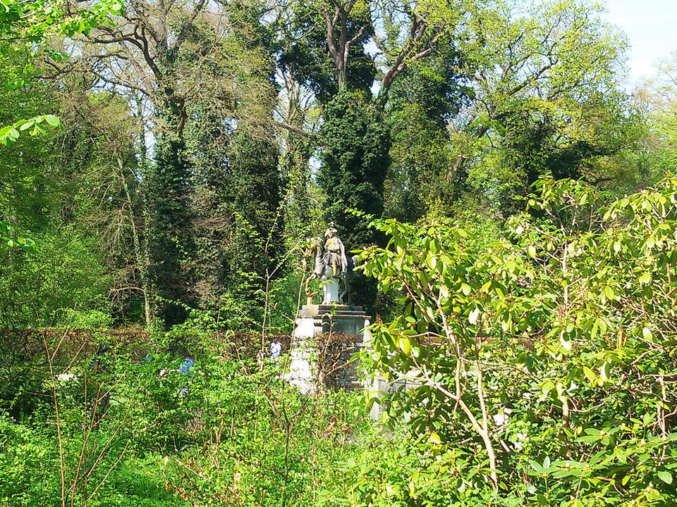 Statue of Frederick the Great at Sanssouci's lush bushes.