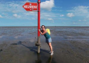 Renata Green with a sign pointing towards Neuwerk when walking on water from Cuxhaven
