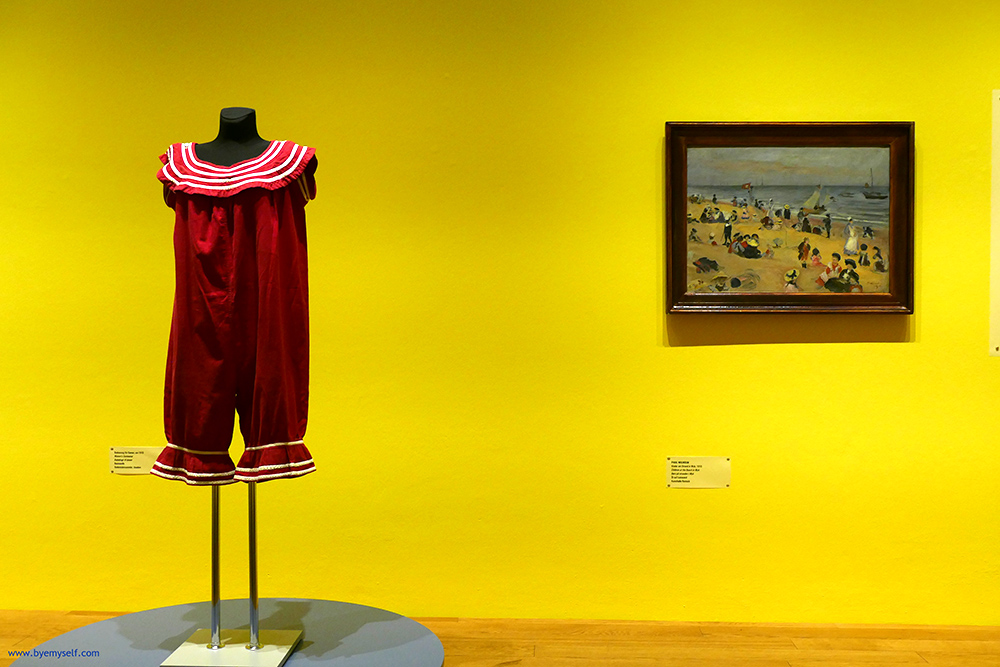 To the left, a woman's swimsuit from 1910, to the right Paul Wilhelm's painting Children at the Beach in Wyk
