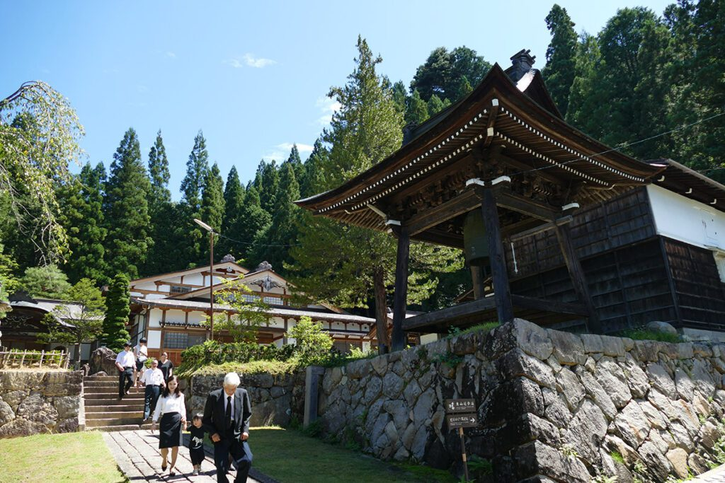 A group of faithful leaving the  Soyuji Temple in TAKAYAMA on a travel back in time and a side trip to SHIRAKAWAGO.