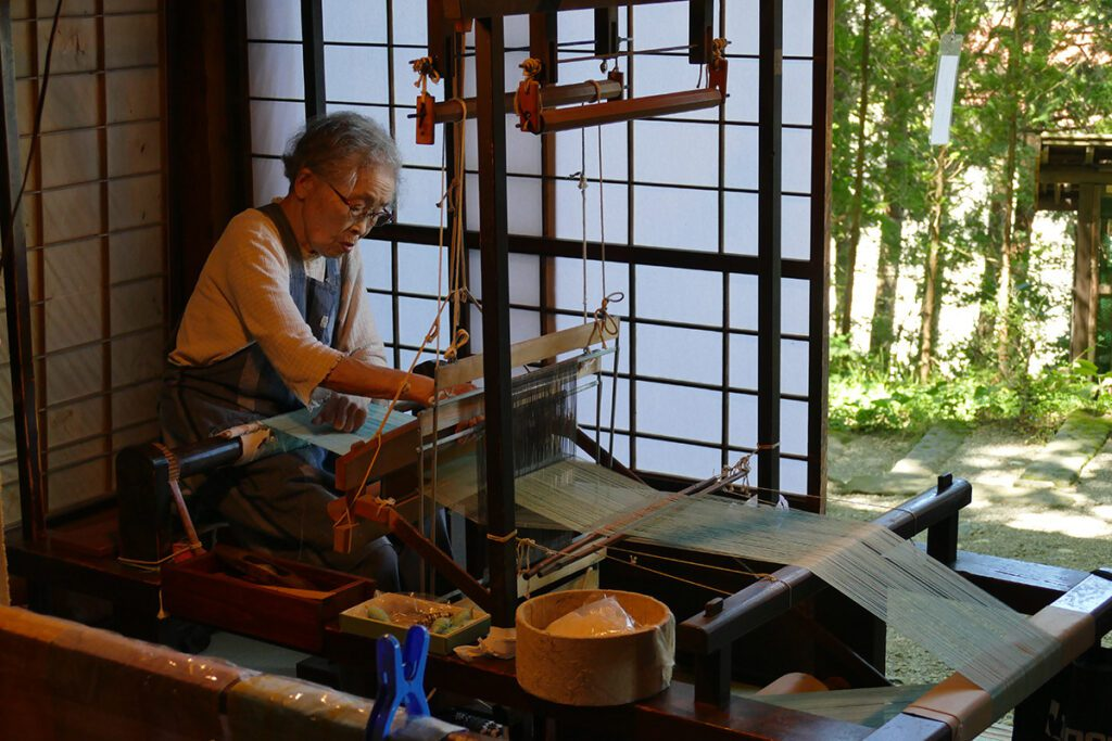 A lady demonstrating how to weave at the Hida Heritage Village in Takayama